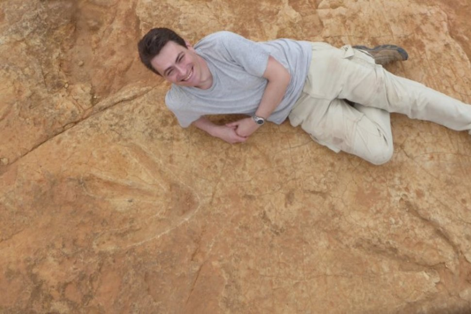 Fabien Knoll, Honorary Senior Research Fellow at the University of Manchester, lies next to the exceptionally large carnivorous dinosaur footprints found in Lesotho, Africa in this undated handout photo obtained by Reuters October 26, 2017. Fabien Knoll/University of Manchester/Handout via REUTERS Reuters